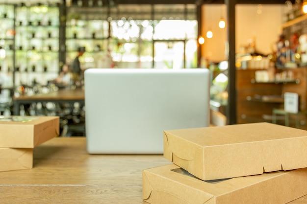 選択したフォーカス小包ボックスパッケージと木製のテーブルの上のノートパソコン。