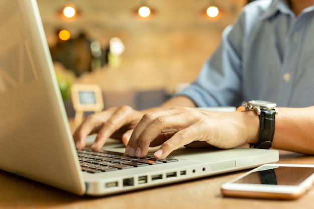 Подрезанное изображение бизнесмена работая на его компьтер-книжке в кофейне.