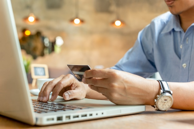 コーヒーショップでラップトップ上のクレジットカードで支払いをする人。
