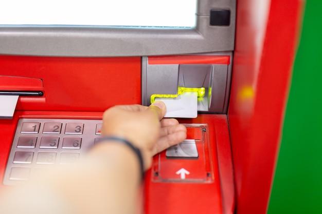 Рука человека с помощью банкомата с кредитной карты.
