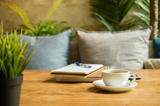 本とコーヒーショップで木製のテーブルの上にペンとコーヒーのカップ。