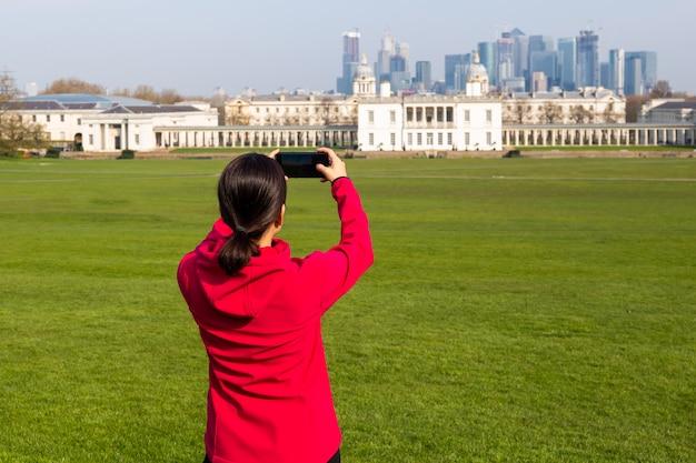 女性観光客が携帯電話で公園の建物の写真を撮る。