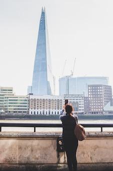 携帯電話で建物とテムズ川の写真を撮る観光客女性。