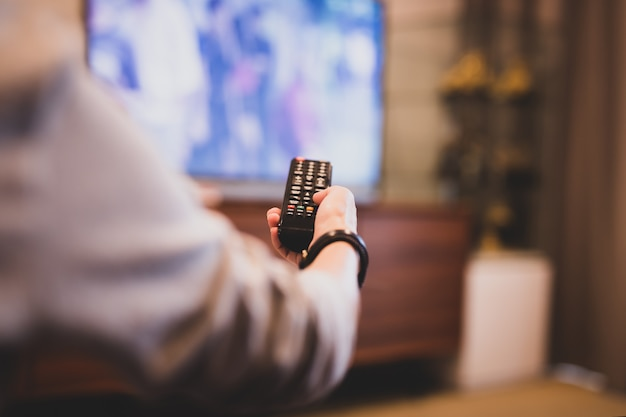 テレビを見るためにリモコンを使って手。
