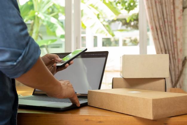 ビジネスマンは小包とテーブルの上のノートパソコンと携帯電話でアイベントリーをチェックします。