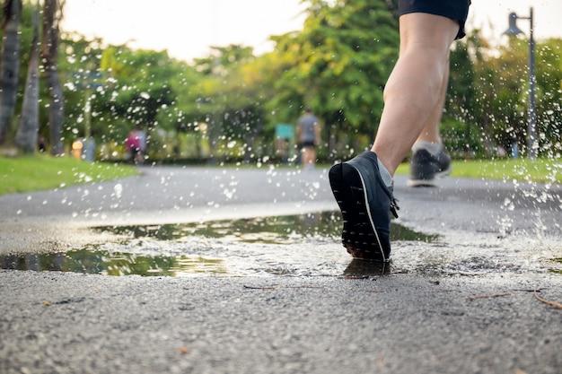 彼の靴をはねかける水たまりを走っている男の運動。