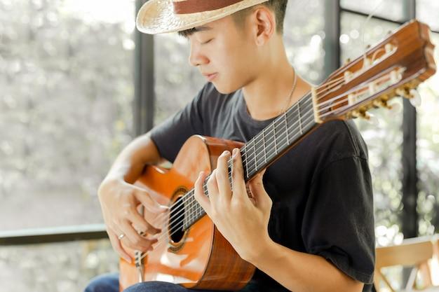 アジア人の男性が彼の目を閉じてクラシックギターを弾きます。