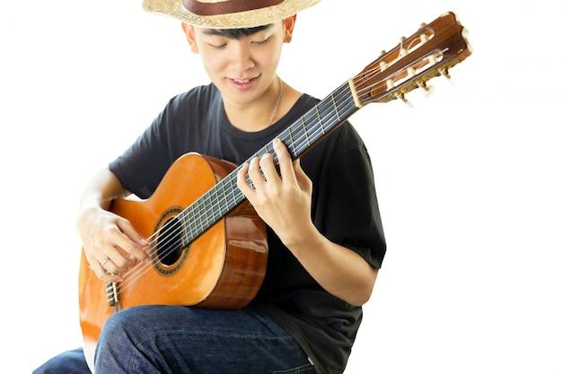 アジア人の男性が白い背景で隔離のクラシックギターを弾きます。