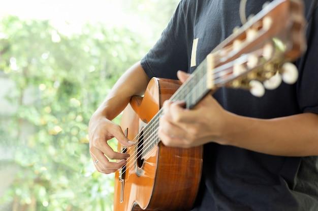 ぼかしのドアでクラシックギターを弾く男
