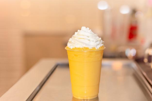 プラスチックガラスの上に新鮮なオレンジのスムージー。