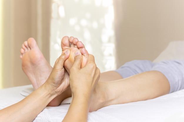 足を持つ女性は、スパサロンでマッサージします。