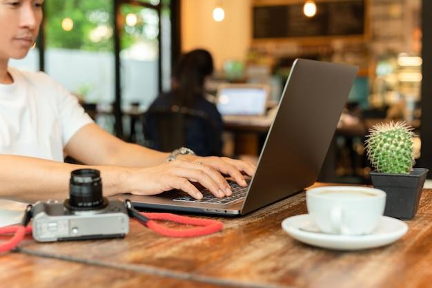 Мужской фрилансер работает на ноутбуке поздно ночью в кафе.