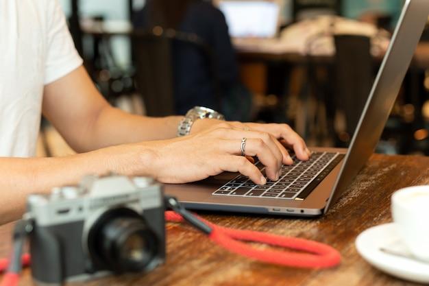 男性の手がテーブルの上のカメラでノートパソコンのキーボードで入力します。