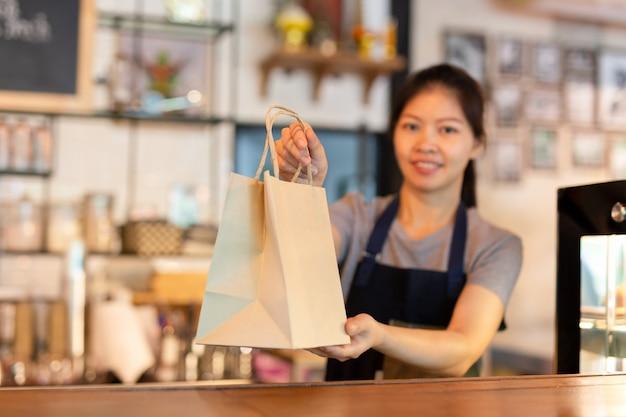 Официантка у прилавка дает экологически чистый бумажный пакет с напитком на вынос в кафе