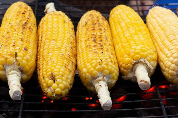 炭火焼きストーブの上の穂軸に焼きトウモロコシ