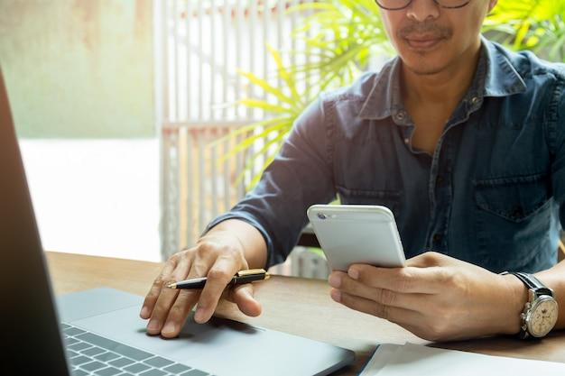 木製の机の上のノートパソコンでの作業中の携帯電話を使用している人の手