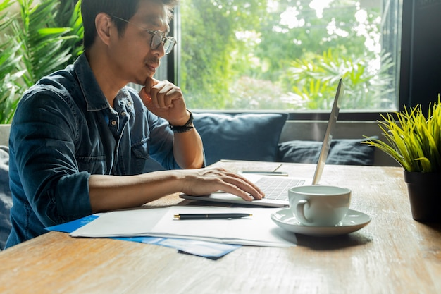 木製の机の上のドキュメント紙とコーヒーカップを持つラップトップに取り組んでいる人