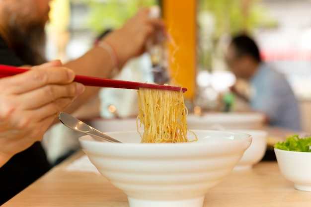 木製のテーブルの上に箸で卵麺を食べる女
