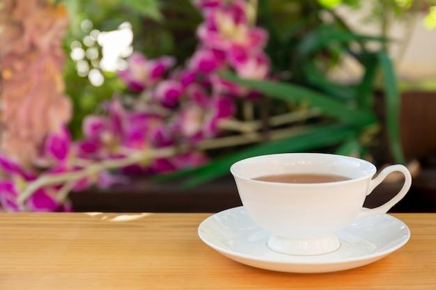 庭の木製のテーブルの上の紅茶のカップ