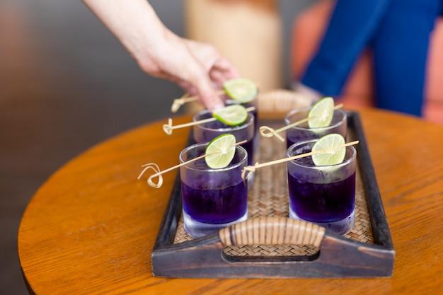 夏の新鮮な飲み物バタフライエンドウ豆の飲み物と竹の皿にライムのスライス。