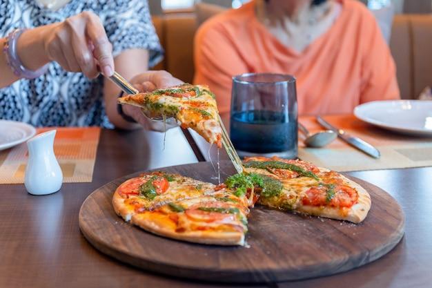 レストランで木の板にピザの部分を拾う女性の手。