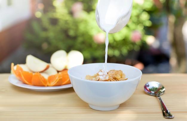 コーンフレークのボウルにミルクを注ぎ、新鮮な果物のプレート