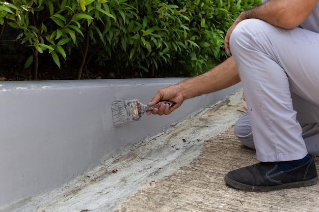 男労働者が絵筆でコンクリートの壁を塗る。