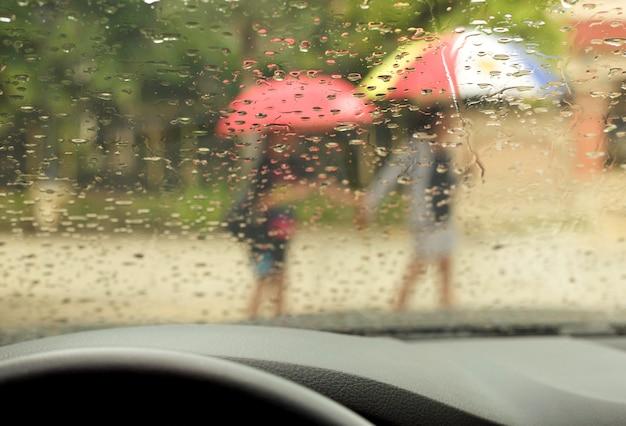 雨の中を歩いている傘を持つ母と息子