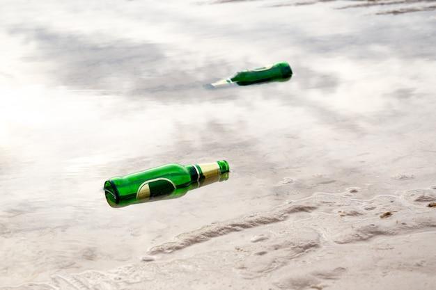 包み込み概念、ビーチで空の緑色のビール瓶。