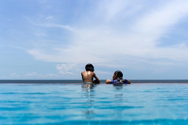 母と幼い息子は、夏休みに海を見渡すスイミングプールでリラックスします。