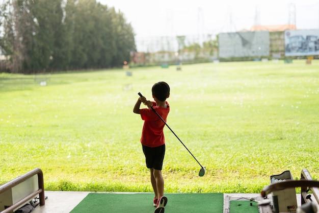 Молодой азиатский мальчик практикует его качание гольфа на тренировочной площадке гольфа.