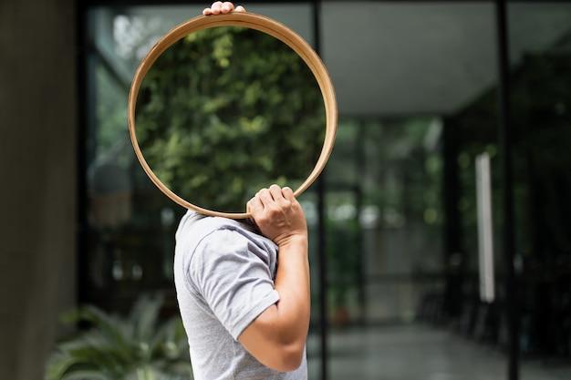 家の装飾用の鏡を運ぶ男。