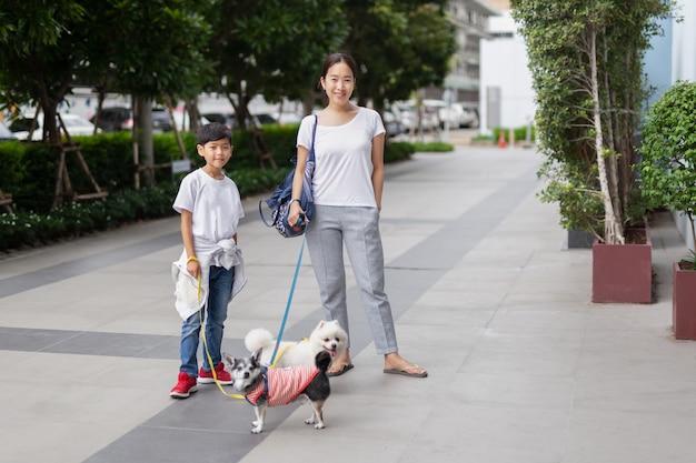 幸せな母と息子が建物の外で犬と一緒に歩いています。