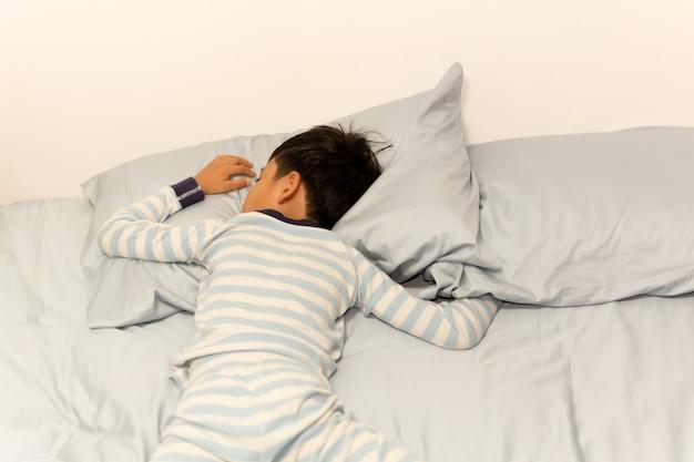 自宅の枕の下で頭をベッドで寝ている少年。