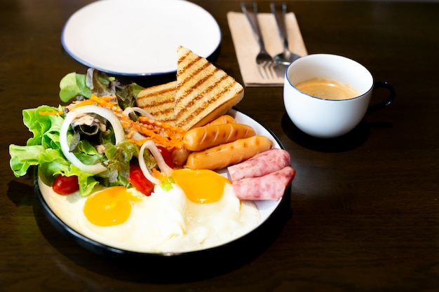 Завтрак, с овощами, ветчиной, беконом, жареными яйцами, колбасой и чашкой кофе.
