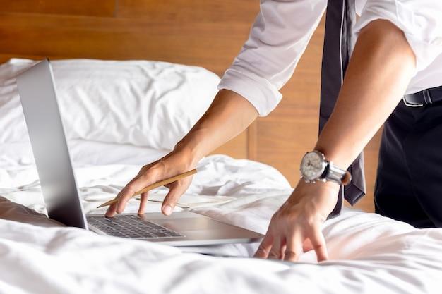 Бизнесмен работает на кровати с ноутбуком