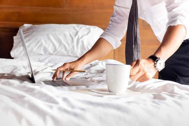 Бизнесмен работает на кровати с ноутбуком, держа чашку кофе