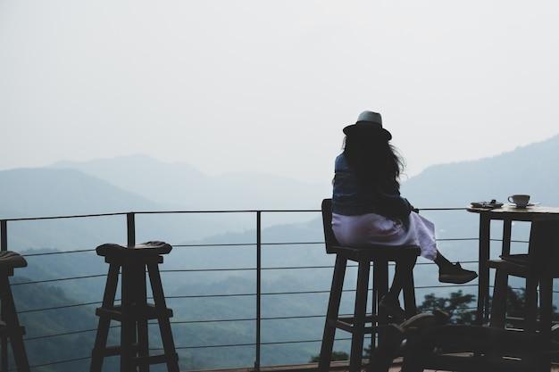 Путешественник женщины сидя вне террасы кафа на верхней части холма и выпивая кофе с красивым горным видом.