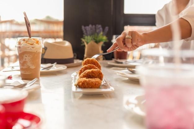 テーブルの上に飲み物と食べ物を取ってフォークを持つ女性の手。