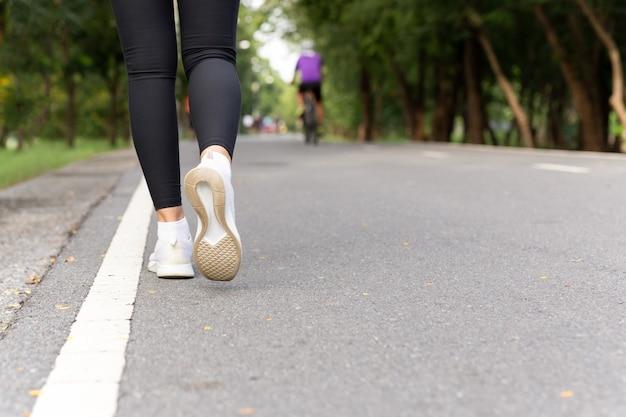 クローズアップアスリートスニーカーは、朝の歩道を歩いて運動します。