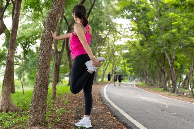 ここで足の筋肉を伸ばす女性は、公園で運動の準備をします。