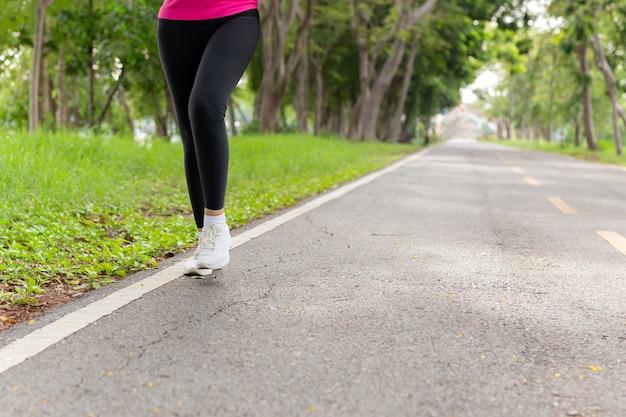 午前中に公園の歩道を歩いてフィットネス女性の足の運動。