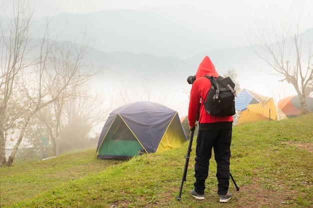 霧の山の写真を撮る三脚とカメラを持つカメラマン。