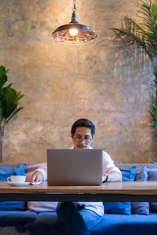 テーブルの上のコーヒーカップとカフェのラップトップで作業する人