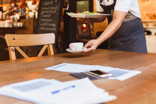 Официант убирает грязную посуду со стола в ресторане.
