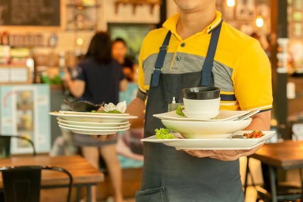 Официант убирает грязную посуду со столиков в ресторане.
