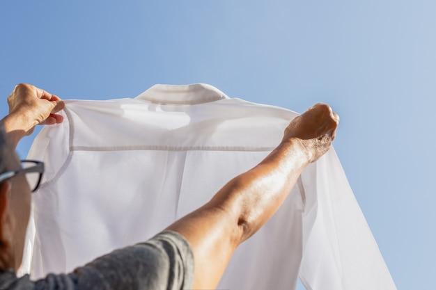 Женщина экономка держит белую рубашку, проверка грязные пятна.