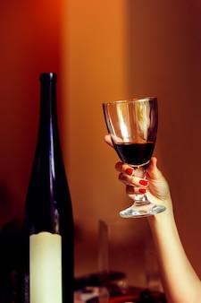 赤ワインのガラスを保持している赤のマニキュアの女性。