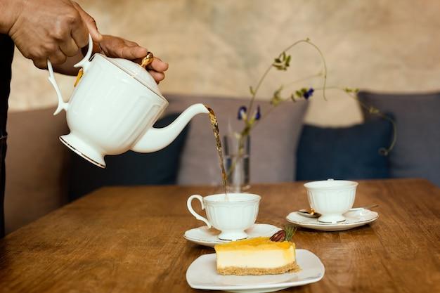 Официант наливая чай с ломтиком лимона чизкейк во время чая.