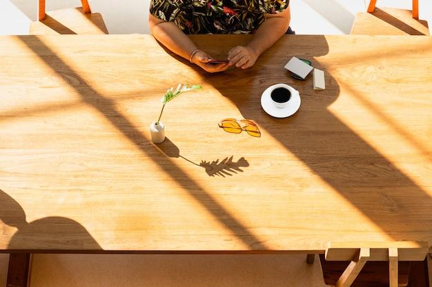 Рука с помощью мобильного телефона с чашкой кофе на деревянный стол.